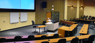 University lecture hall with technology and screen at the front of the room.