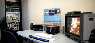 Video editing suite with computer, monitor and sound equipment.