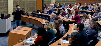 Conference speaker and attendees in lecture hall.