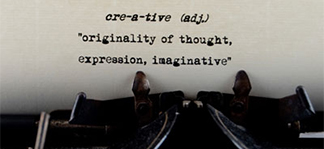 "Typewriter typing the message ""cre-a-tive (adj.) originality of thought, expression, imaginative"""