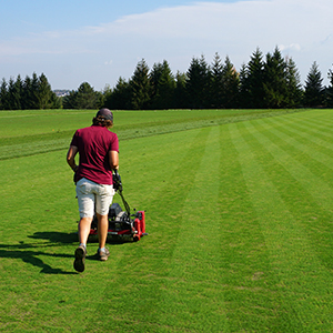 Man mowing a large area of grass.